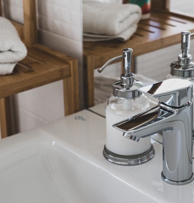 stainless-steel-faucet-on-white-ceramic-sink-3761560